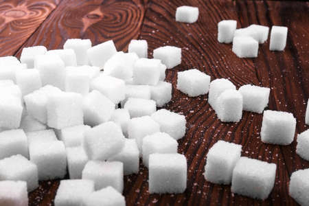 Many cubes of white sugar on a dark brown wooden table. Consumption of bad calories. White organic sugar and sweet food ingredient on the table.
