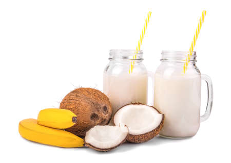 sweetly: A composition of a whole and cut, fresh, organic coconuts, two tasty, sweetly bright yellow bananas and two mason jar full of natural, fresh coconut milk with yellow straws, isolated on a white background. Stock Photo