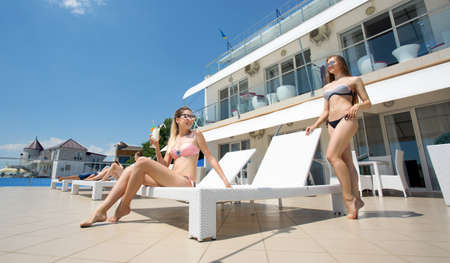 Two beautiful girls in bright swimsuits against the backdrop of an expensive hotel. Charming blonde sunbathing on a deck chair and next to her the full-length is a hot brunette in a black swimsuit.