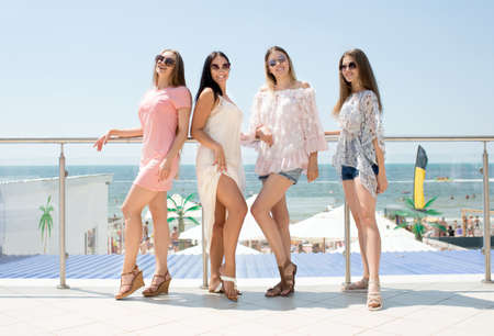 Summertime portrait of charming and young women in light clothes and with elegant sunglasses are posing on sea background and looking happy. Beautiful ladies in multi-colored clothes in the summertime on a sea background. Stock Photo