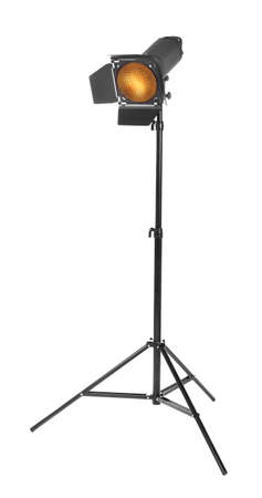 spotlight: Studio lighting on a tripod stand, isolated on a white background. Spot light photography equipment. The photo of the honeycomb is glowing.