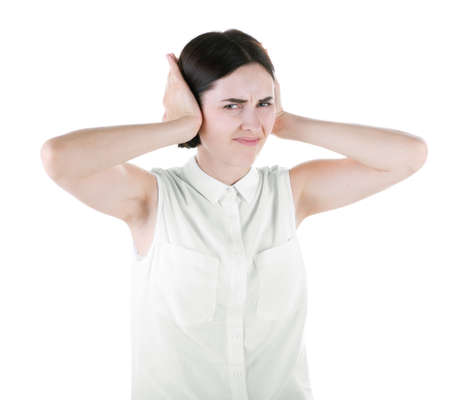 An adorable brunette female isolated over the white background. A shocked, disgusted woman closing her ears with hands. A judging girl with short hair wearing a casual shirt. Stock Photo