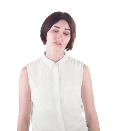 A sad and awkward office lady isolated over the white background. A disgusted young woman in a light and loose casual blouse. A disappointed and unpleased brunette girl.