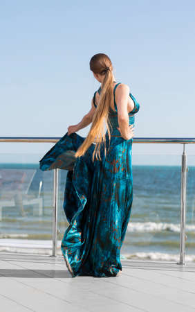 A charming girl in a long green dress is in a beautiful position on a transparent balcony on a blue sea background. The cute lady holding the long dress, flutters in the wind.