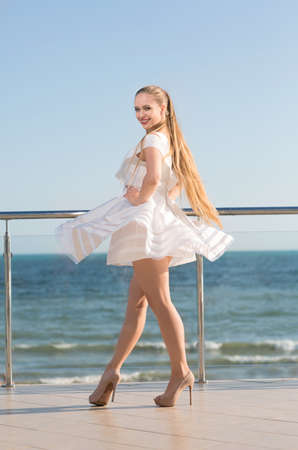 A fashionable gorgeous lady on a transparent terrace on a bright blue sky background. A stylish girl with a long dark blond ponytail. A joyful young woman in a white dress outside.