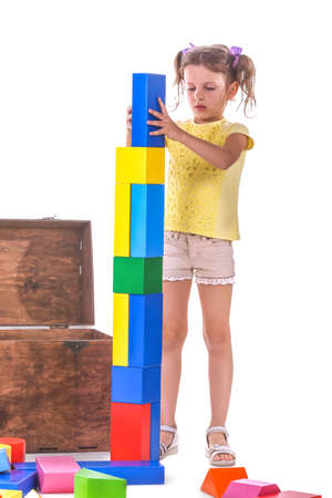 An adorable little girl with toy-bricks isolated on a white background. A pretty child with two ponytails in yellow shirt playing with many colorful bricks. A spacious wooden box for developing toys.
