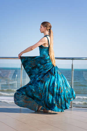 An attractive young model in a long waving emerald dress is posing on a blue sea background. The charming woman is posing near the sea beach. The stylish woman near the sea. Stock Photo