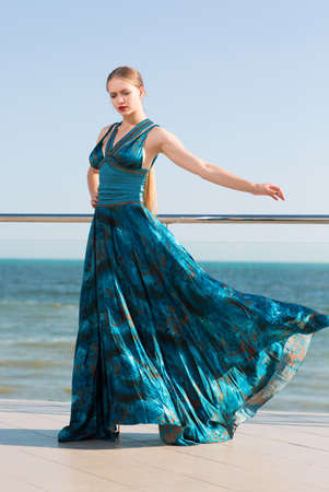 A beautiful and young woman with blinde hair and in a long waving emerald dress on a blue sea background. An attractive girl in a long dark blue dress, that flutters in the wind, full-length. Stock Photo