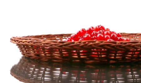 Healthful red currant in a brown basket isolated over the white background.  Juicy seasonal berries. Delicious red currant for a breakfast. Rustic berries for vegetarian snacks. Stock Photo