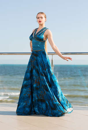 Full-length portrait of a handsome woman in a long waving emerald dress on a blue sky background. The girl in a long turquoise dress, that flutters in the wind. A concept of femininity, harmony.
