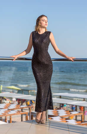 Full-length photo of a luxurious lady is posing on a transparent balcony on a bright blue natural background. The girl in a long black dress is enjoying a sunny summer.