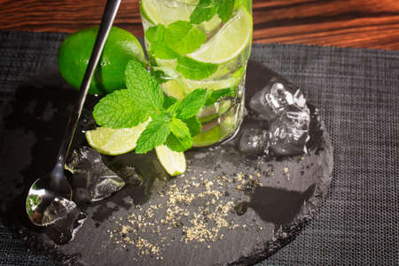 Summer colourful beverage with fresh lime segments, whole lime ice cubes and leaves of peppermint on a black napkin. A transparent highball glass with a long tea-spoon on the wooden table. Stock Photo