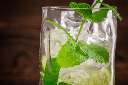 Close-up of a tasty organic beverage with fresh slices of lime, ice and leaves of mint on a wooden background. Summer refreshing beverages for parties. Stock Photo