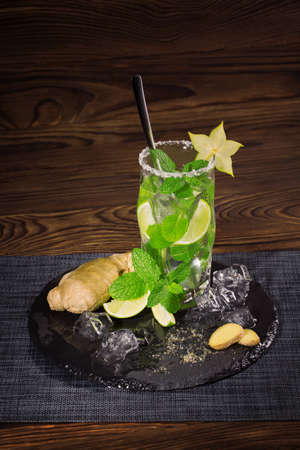 Delicious natural beverage with fresh lime segments, carambola, ice, ginger and leaves of mint. Bright cocktail in a transparent highball glass on the black tablecloth on a wooden background.
