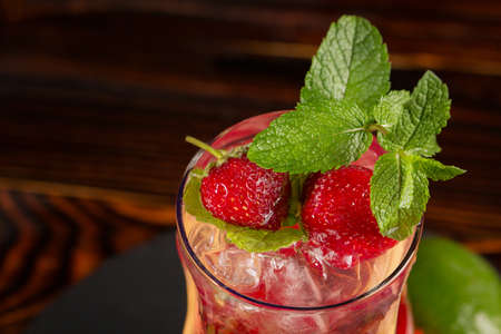 Top view of a fresh organic beverage with ripe strawberry slices, lemon, ice cubes and leaves of peppermint isolated on a wooden background. Strawberry cocktail in a transparent glass.