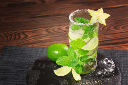 A huge glass filled with alcohol mojito on a light brown wooden background. A cold mojito with liquor, green mint and decorative carambola. A refreshing mojito for summer parties. Copy space.