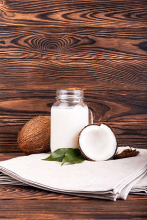 A beautiful composition of a mason jar with fresh milk and coconuts on a gray piece of cloth on a wooden background. Whole and half in a cut coconuts with green leaves on a brown table.