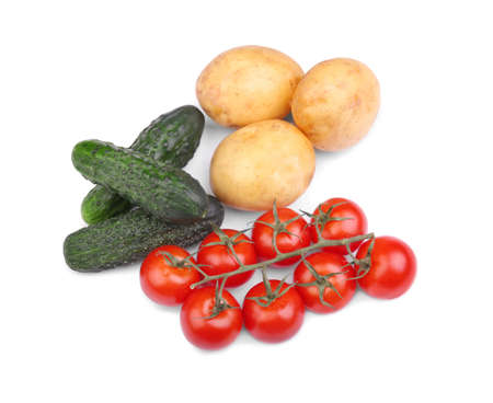 A top view of freshly picked vegetables isolated on a white background. Juicy green cucumbers, a red bunch of healthy tomatoes and nutritious peeled potatoes. Ingredients for traditional salads.