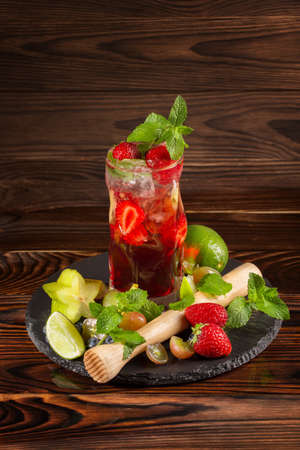 Close picture of a cool bright beverage with fresh slices of strawberry and lime, ice, carambola and mint twigs on the wooden background. Refreshing strawberry cocktail for party. Copy space.