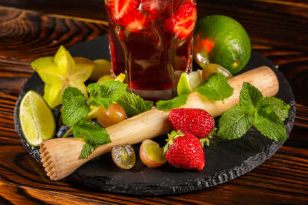 Close-up picture of a colourful organic strawberry beverage with fresh slices of strawberry and lime, carambola and mint twigs  on a wooden background. Refreshing cocktail in a highball glass. Stock Photo