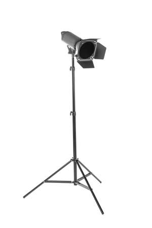 Studio flash with barn door, isolated on a white background. Photo-studio with lighting equipment. Studio lighting on a tripod stand. Spot light photography equipment. Stock Photo