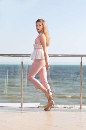 Une femme à la mode et jeune en talons hauts et en costume rose clair sur fond de mer d'été. Une fille magnifique avec un corps parfait et aux cheveux brun clair se pose sur un balcon en verre.