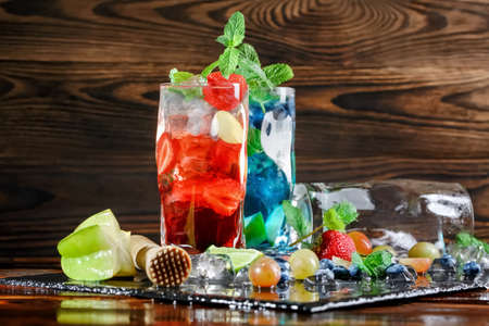 A beautiful composition of strawberry and blueberry mojito. Two glasses of mojitos on a dark wooden background. Juicy berries, mint leaves, ice cubes, cut fruits and lime on a black plate. Copy space. Stock Photo