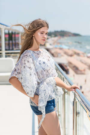 A beautiful young girl in a light summer blouse and short denim shorts on the background of an expensive hotel near the sea. A cute girl stands sideways and her long fair-haired hair fluttering in the wind.