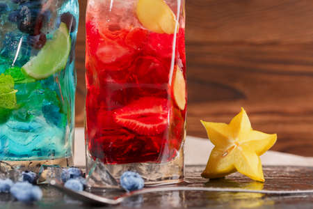 Close-up of blue and red drinks on a wooden background. Two summer refreshing cocktails with mint, blueberries, strawberries, grapes, cubes of ice and decorative carambola in transparent glasses.