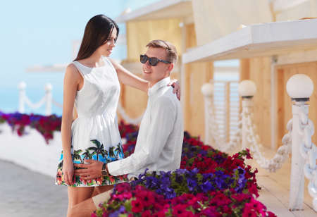 Boyfriend and girlfriend on a date. Easy going and beautiful young lovers. A romantic couple on a colorful resort background.