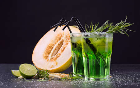 Refreshing non-alcohol drinks. Cut melon and green cocktails on a black background. Sweet drinks with liquor, lime and tarragon. Stock Photo