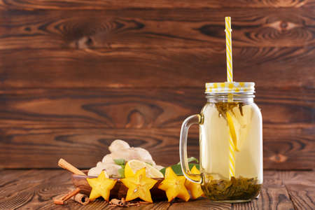 Green lemon tea in a big glass jar with straw next to cut lemon, cinnamon, ginger, and carambola on a wooden background. Copy space.