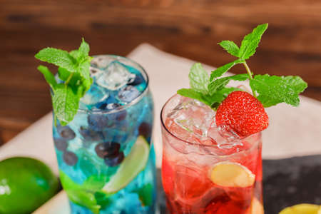 Top view picture of blue and red beverages on a wooden background. Refreshing bright cocktails with mint, slices of lime, strawberries, grapes and ice cubes  in transparent highball glasses. Stock Photo