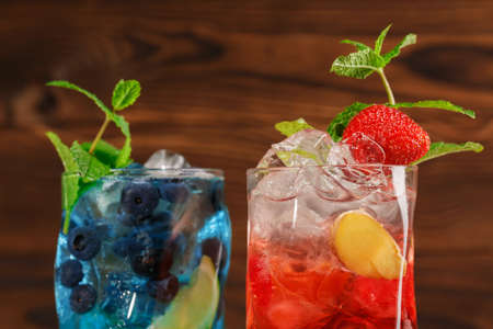 Close-up of blue and red drinks. Two tasty bright summer beverages with mint twigs, blueberries, strawberries, ice and ginger in cocktail glasses on the wooden background. Alcoholic drinks.