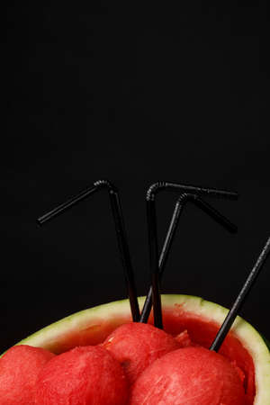 Colorful, fresh, sliced watermelon on a black background. Red and juicy watermelon scoops. An opened watermelon with black straws. Refreshing and healthful summer fruits for a vegetarian breakfast.