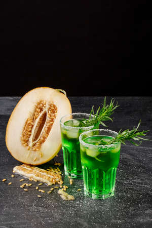 Cantaloupe: A couple of glasses full of non-alcohol and organic cold drinks and a cut in half cantaloupe melon on a black background. Juicy melon honeydew and sweet lime drinks with tarragon leaves on a table. Stock Photo