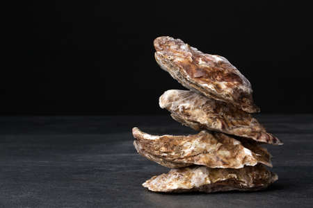A small pile of four close juicy oysters on a black background. Fresh tropical sea mollusks full of nutrients. Close seashells. Expensive food. The greatest delicacy. Healthy food. Stock Photo