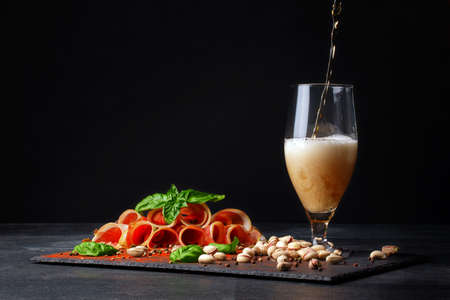Cured prosciutto with a basil and a goblet of alcoholic beer with foam on a black background. Salty nuts, tasty ham slices. and a glass of beer. Copy space.