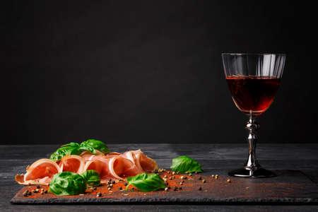 hams: Una hermosa composición de comida deliciosa o aperitivos sobre un fondo negro saturado. Una copa de vino llena, carne tirada y albahaca picante en el escritorio. Prosciutto sabroso y vino semi dulce. Copie el espacio.