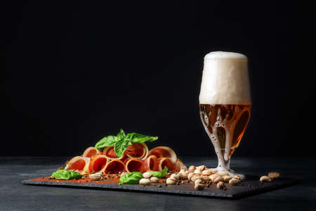 intoxicating: A delicious Italian ham cured by drying and served in thin slices on the saturated black background. A glass of intoxicating beer with foam. Tasty prosciutto and pistachios on the table. Stock Photo