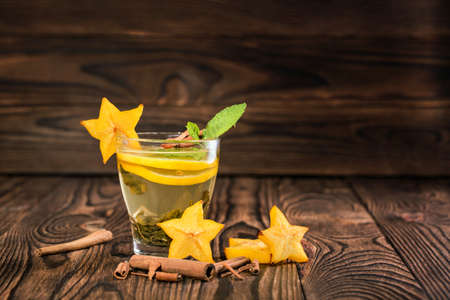 Beautiful cup of tea. Green tea on a wooden background. Mint tea with lemon, decorative carambola, cinnamon. Copy space. Stock Photo
