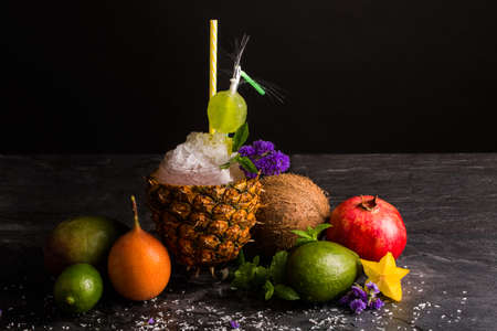 A big pineapple cup with multifruit juice and cracked ice on a saturated black background. Carambola, refreshing garnet, juicy coconut, green avocado with mint and violet flowers. Stock Photo