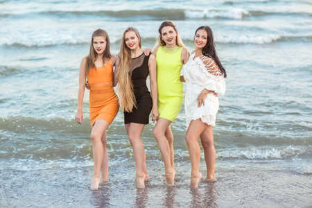 Four beautiful young girls stand in the background of a sea shore, full-lengths. Charming young women in multi-colored dresses.