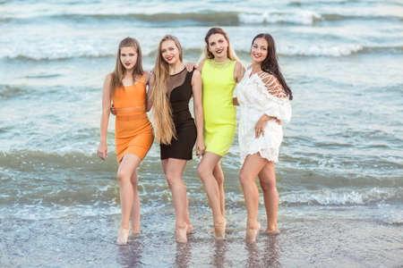 Vier mooie jonge meisjes staan op de achtergrond van een kust, van gemiddelde lengte. Charmante jonge vrouwen in veelkleurige jurken.