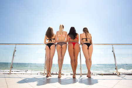Sexy girls on a summer vacation. Stunning young women relaxing on a sunny balcony. Girls in bikinis. Sunbathing on a beach.