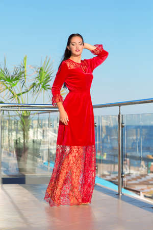 velvet dress: A beautiful woman posing on a blue sky background. A confident girl in a red dress smiling. A brunette lady on a hotel terrace. Stock Photo