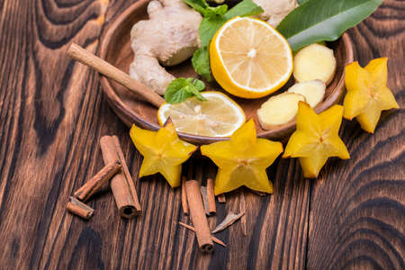 Close-up of a plate with sour lemon, spicy cinnamon sticks, yellow carambola and ginger on a wooden background. Cut carambola and lemon. Organic ingredients for healthy tea full of vitamins.
