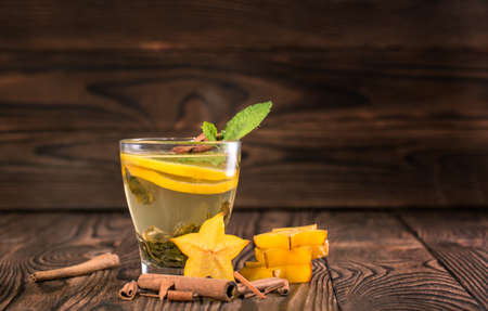 Close-up picture of a colorful green tea with slices of lemon on a wooden blurred background. A small cup full of a hot tea with cinnamon and mint. Stars of carambola near the cup. Copy space.