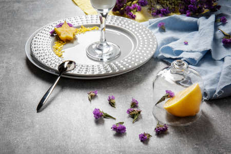 A bright set of flowers, plates and tropical fruits on a light gray table background. Blue and yellow fabric next to a plate with a tall glass, carambola and petals. Beautiful summer compositions.