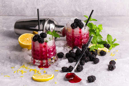 Couple of fancy glasses full of cold, icy beverage with spearmint, lemon pieces, juicy blackberries and black straws on a frozen gray table background. Refreshing cocktails with fruits and berries. Stock fotó - 83588115